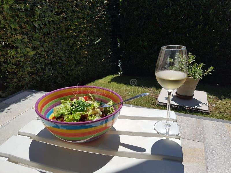 Un día de verano con una ensalada y un vidrio de vino blanco en el jardín imagen de archivo