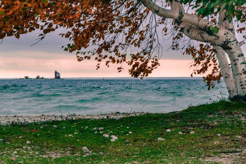 Un día ventoso de la caída en la isla de Mackinac, mirando hacia fuera el faro redondo de la isla fotos de archivo libres de regalías