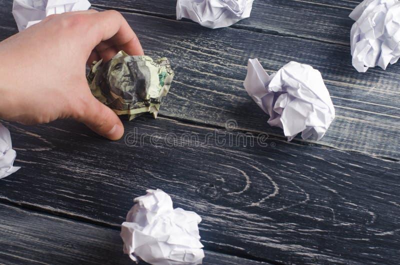Un dólar arrugado en una tabla al lado de bolas del Libro Blanco El proceso de pensar y de encontrar nuevas ideas del negocio, re fotos de archivo