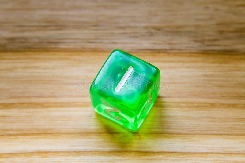 Un dado que juega exagonal verde translúcido en un backgroun de madera fotos de archivo