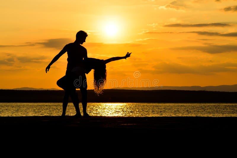 Un dancing delle coppie dal mare al tramonto fotografia stock libera da diritti