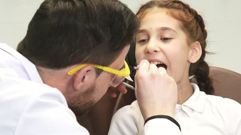 Un dentista atento examina a su pequeño paciente imágenes de archivo libres de regalías