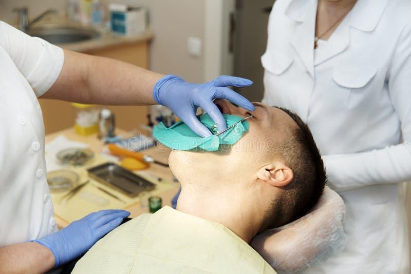 Un dentista con assistenti nella pratica dentaria fotografia stock