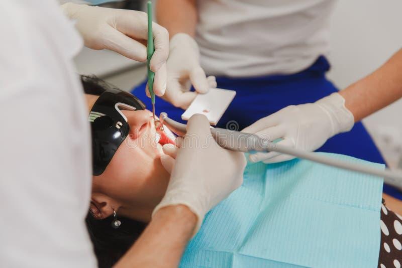 Un dentista de sexo masculino con un ayudante femenino ayuda a tratar los dientes de un paciente de la mujer en una clínica en la fotografía de archivo