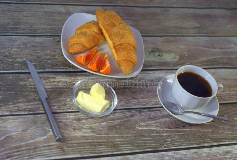 Un desayuno caluroso, una placa con dos cruasanes y rebanadas frescos de naranja, una taza de café sólo y mantequilla con un cuch fotos de archivo libres de regalías