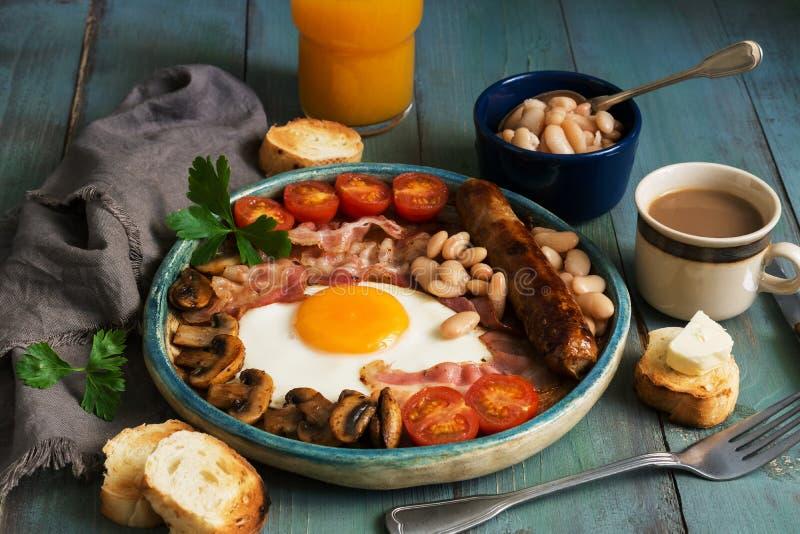 Un desayuno inglés lleno tradicional con el huevo frito, la salchicha, las setas, las habas, el tocino y los tomates en una tabla imagenes de archivo