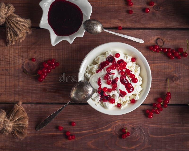 Un desayuno ligero del requesón con crema agria, bayas y atasco de la pasa roja, una cuchara, y atasco de la pasa en un cuenco po foto de archivo libre de regalías