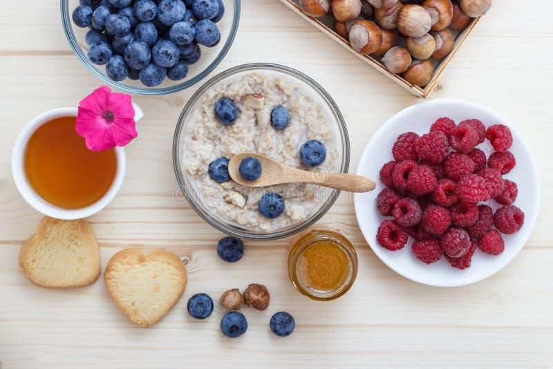 Un desayuno sano de la harina de avena, de arándanos, de frambuesas, de avellanas, del té con la miel y de galletas foto de archivo libre de regalías