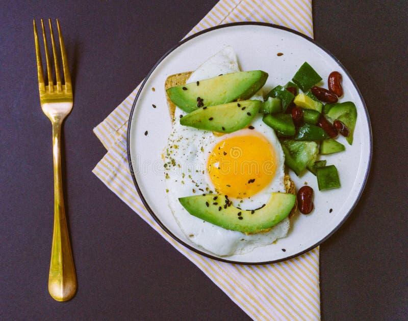 Un desayuno sano de la tostada con el aguacate, pan del trigo integral y huevo frito y ensalada del burrito en la placa blanca foto de archivo