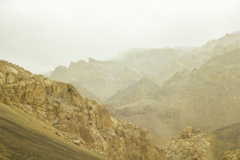 Un desierto de la montaña con las colinas arenosas en las nubes fotografía de archivo
