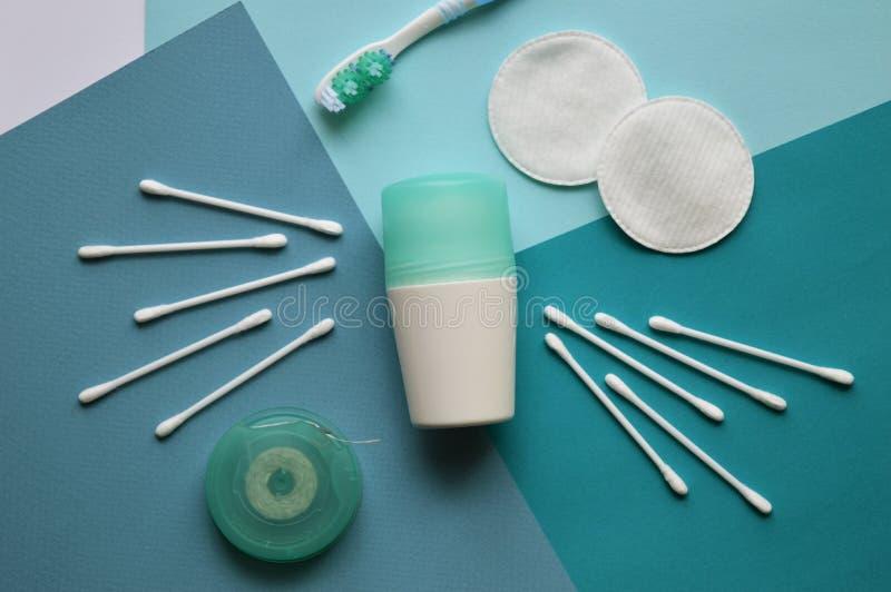 Un desodorante, cojines de algodón para la cara y los brotes para los oídos, brushtooth y seda dental en el fondo azul de diverso fotos de archivo libres de regalías