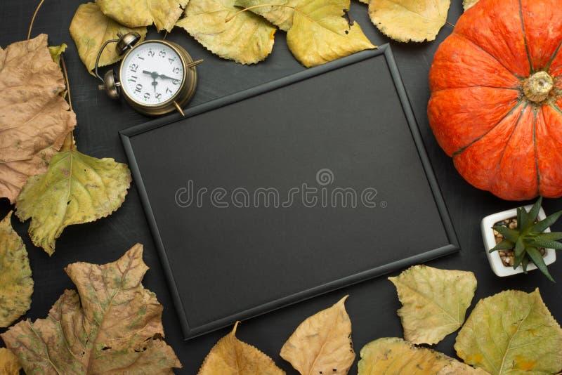 un despertador, un follaje de la calabaza y del otoño y un marco negro vacío opinión superior puesta plana de los alimentos de la fotos de archivo libres de regalías