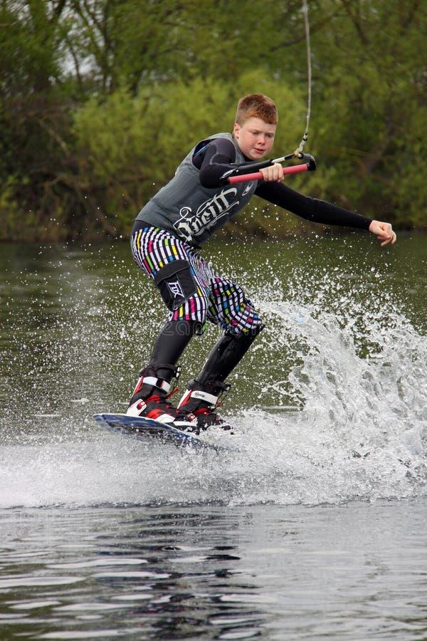 Un despertar-embarque del hombre joven/el practicar surf imagen de archivo