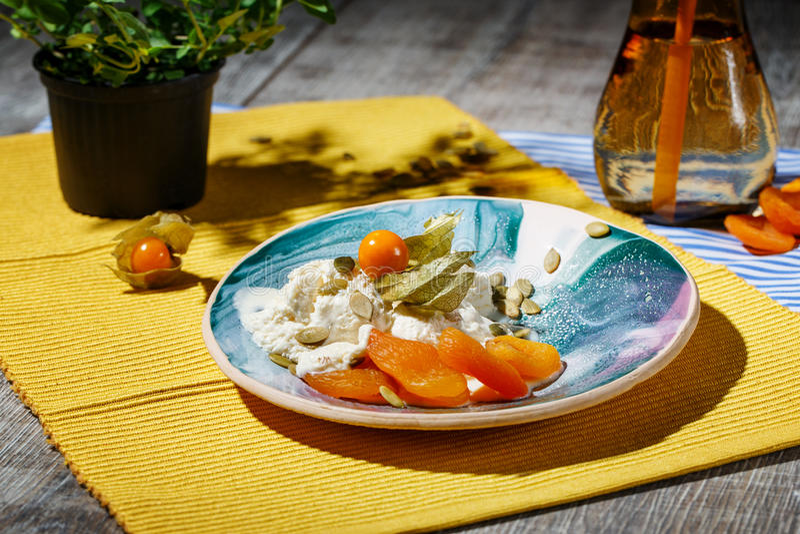 Un dessert con il physalis e frutti secchi su un piatto e su un tessuto Una bevanda calda vicino ad un gelato su un di legno immagini stock libere da diritti