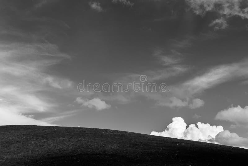 Un dessus de colline sous un ciel profond, avec un blanc et fluffly un nuage images stock