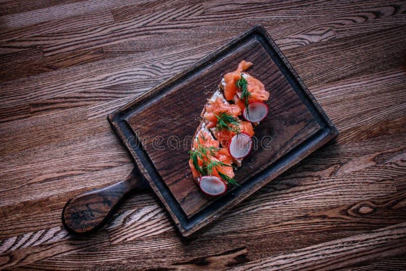 Un dessus de table en bois sur lequel se trouve un panneau des sandwichs avec le salmo image libre de droits