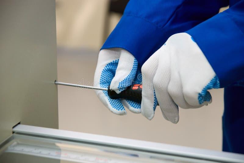 Un destornillador en mano del guante imagenes de archivo