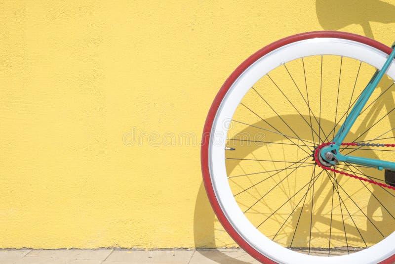 Un dettaglio del primo piano della ruota dentata su una bicicletta d'annata contro una parete gialla immagini stock