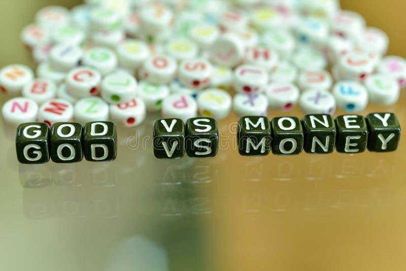 Un DIEU CONTRE L'ARGENT écrit avec le cube noir acrylique avec les perles blanches d'alphabet sur le fond en verre image libre de droits