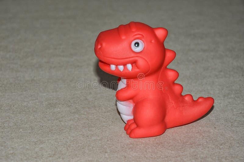 Un dinosaurio del juguete rojo del juguete de los niños fotos de archivo libres de regalías