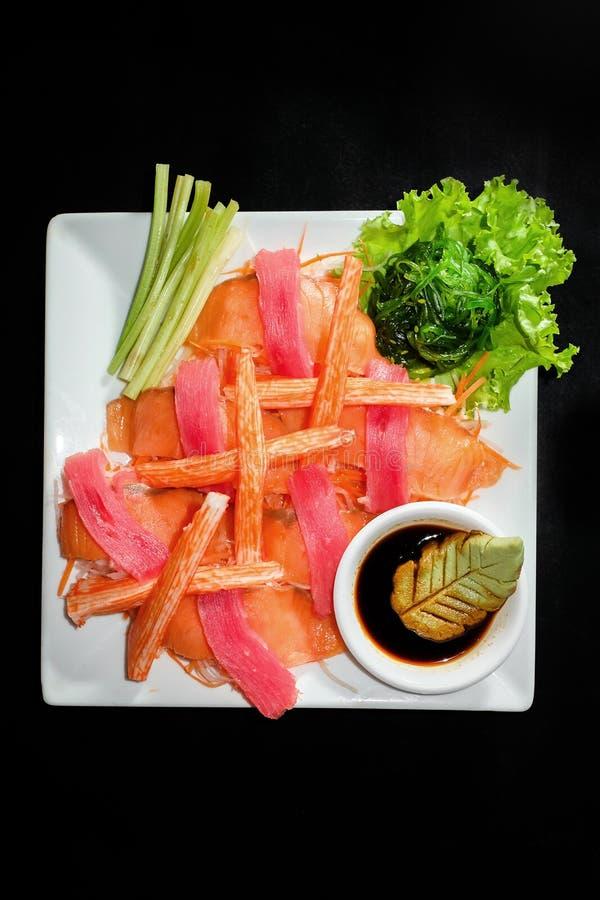 Un disco colorido del sushi del sashimi con los palillos del atún y del cangrejo fotos de archivo