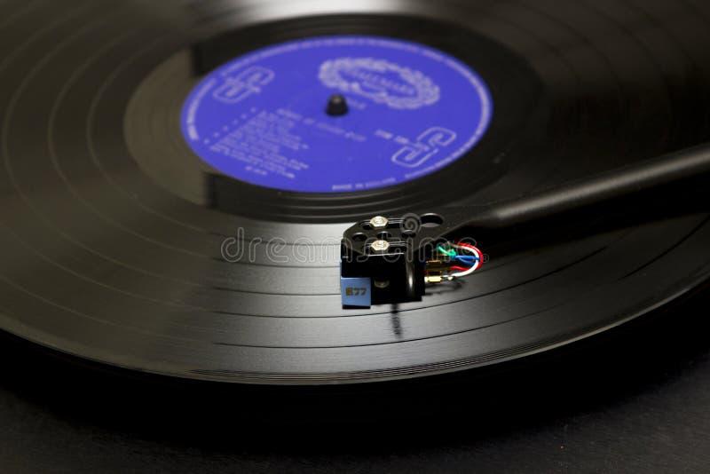 Un disco de vinilo de disco de larga duración en una placa giratoria con el brazo de fonocaptor y cartucho en el condado de Bango imagen de archivo