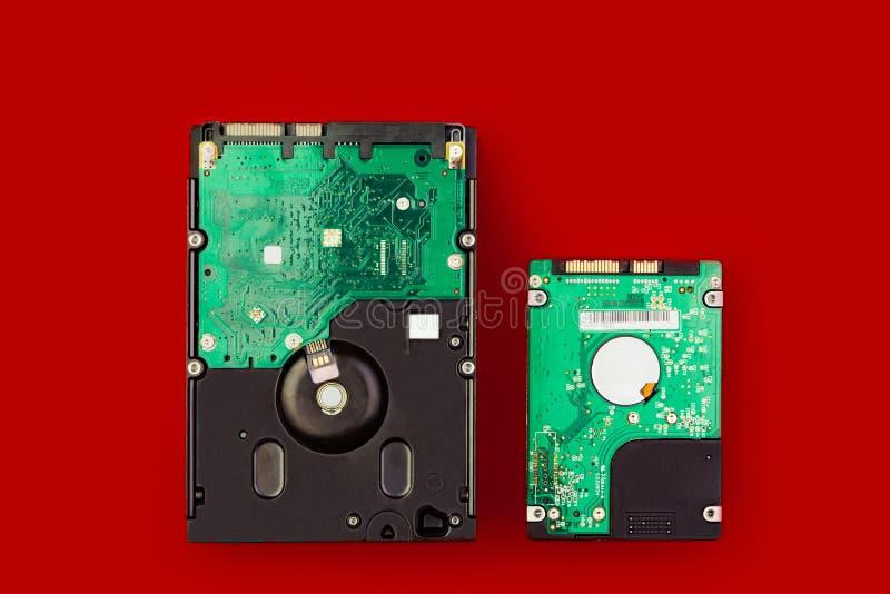 Un disco duro grande y un pequeño hdd en un fondo rojo fotografía de archivo libre de regalías