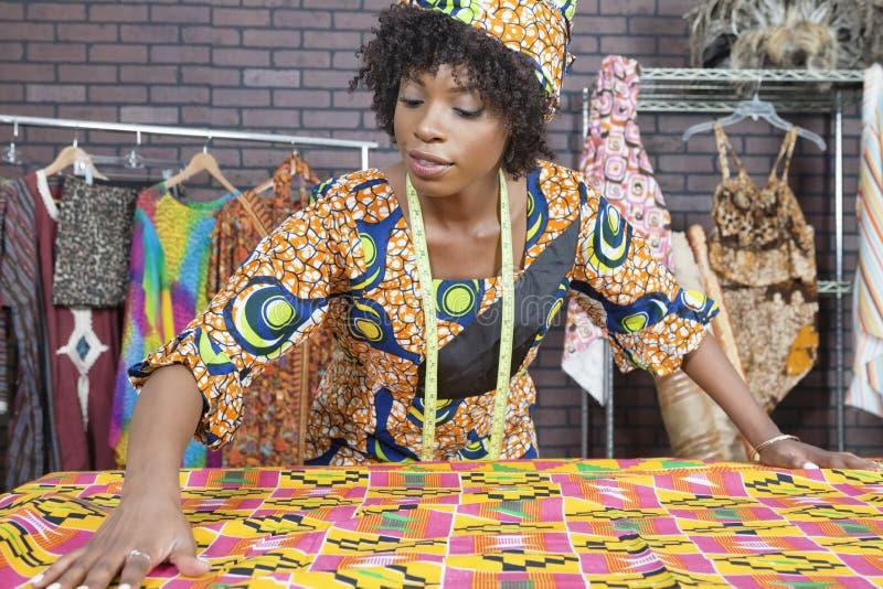 Un diseñador de moda de sexo femenino afroamericano que trabaja en un paño del modelo fotos de archivo libres de regalías