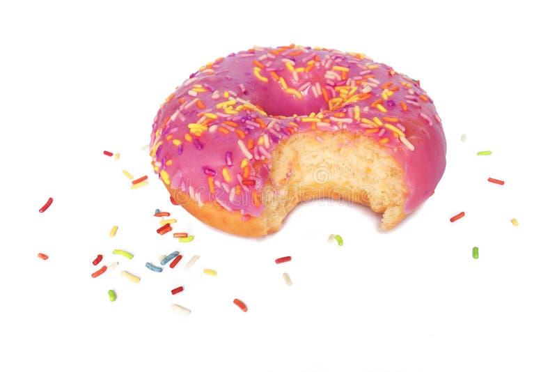 Un disparus de morsure de beignet avec le givrage rose et le sucre coloré arrosent d'isolement sur le fond blanc photo stock