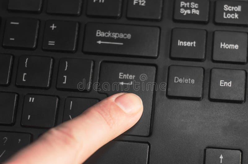 Un dito che preme il ` fornisce la chiave del ` sulla tastiera nera immagine stock