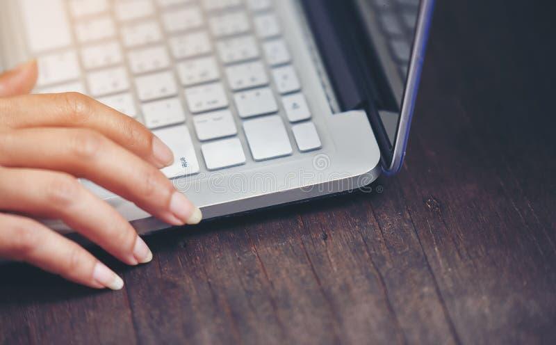 Un dito della donna sta premendo il tasto dell'introduzione sulla sua tastiera fotografia stock libera da diritti