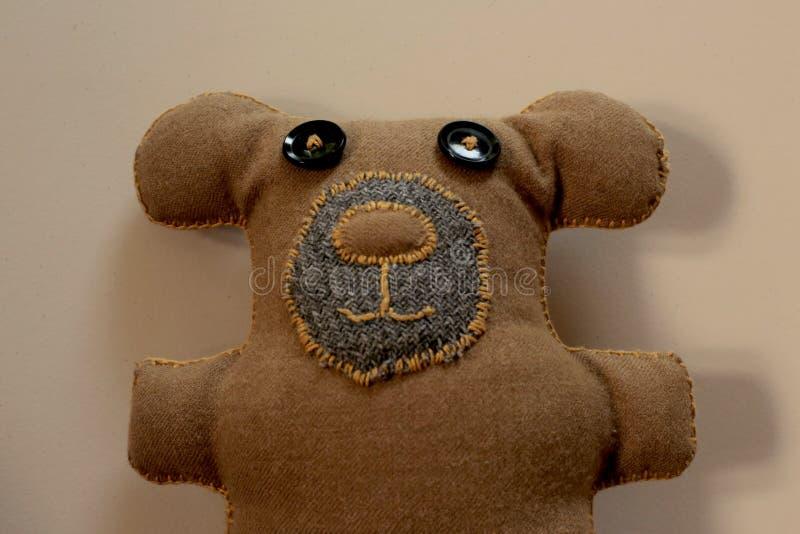Un DIY Mano-cosió el oso de peluche de Brown con la manta que cosía y el botón negro observa foto de archivo