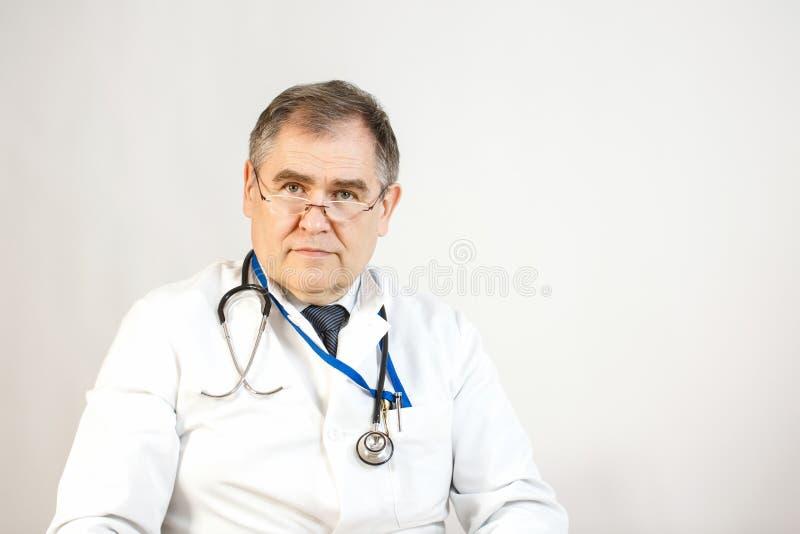 Un docteur dans un manteau et un lien blancs regarde en avant, un whist a un stéthoscope et un insigne sur son cou, et il y a des photos stock