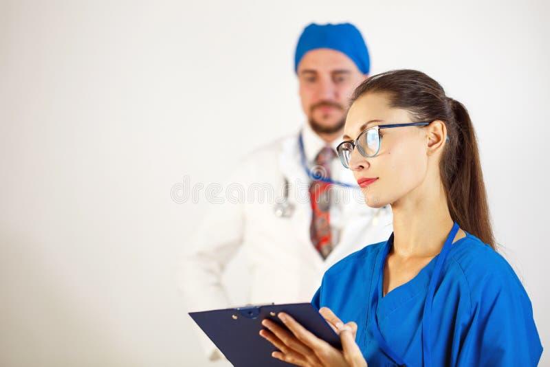 Un docteur féminin avec des verres tient un journal dans des ses mains, à l'arrière-plan est un docteur masculin Fond blanc photographie stock libre de droits