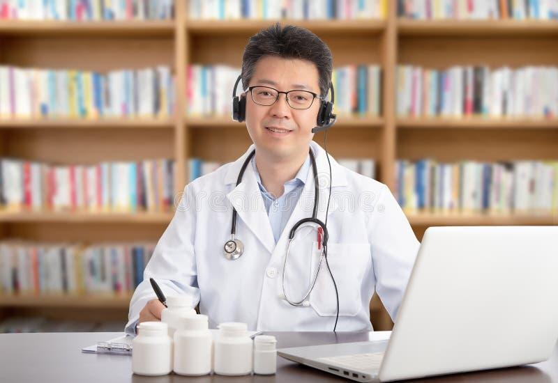 Un doctor asiático que está consultando remotamente con un paciente Concepto de Telehealth fotografía de archivo libre de regalías
