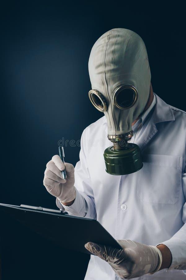 Un doctor asustadizo en la careta antigás que sostiene una pluma y un tablero fotos de archivo libres de regalías