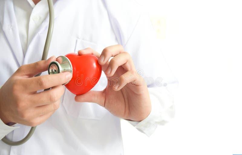 Un doctor con el estetoscopio que examina atención sanitaria roja del corazón y concepto médico foto de archivo
