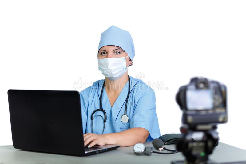 Un doctor de la mujer en una máscara está mecanografiando en un ordenador en los lanzamientos blancos de una cámara del fondo imagen de archivo