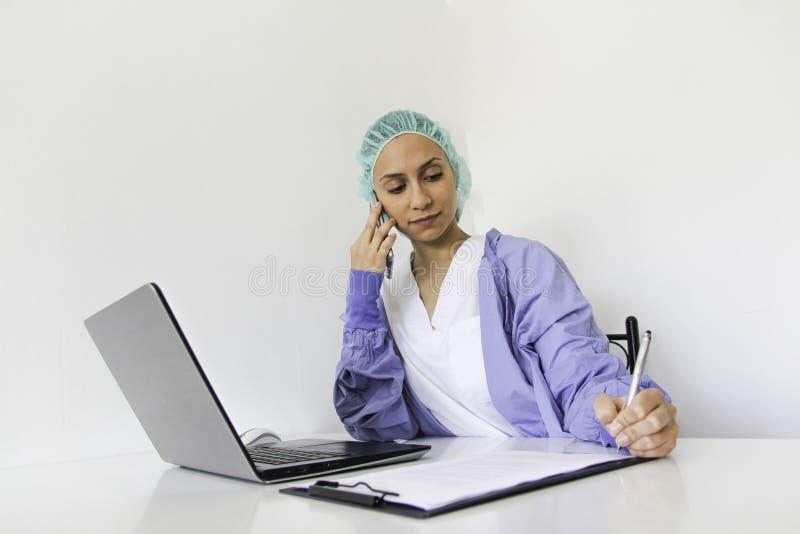 Un doctor With de mujer joven un ordenador portátil en su oficina que habla en el teléfono imagen de archivo