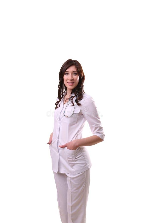 Un doctor de sexo femenino con las manos en bolsillos dura, colocando o aislado fotos de archivo