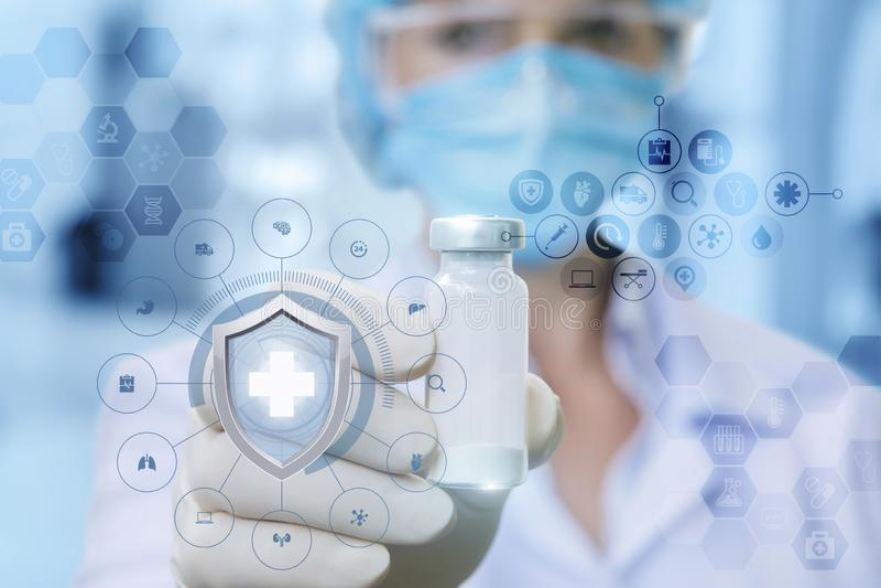 Un doctor de sexo femenino en la máscara médica está mostrando una vacuna en su mano en el guante de goma foto de archivo