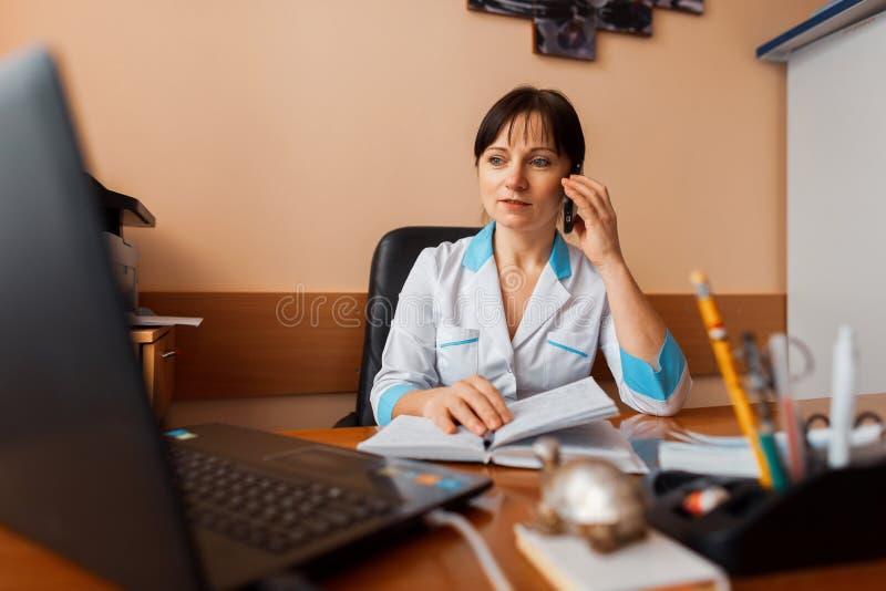 Un doctor de sexo femenino en una capa blanca se sienta en su tabla en la oficina, mirando un ordenador portátil y hablando en el imagen de archivo