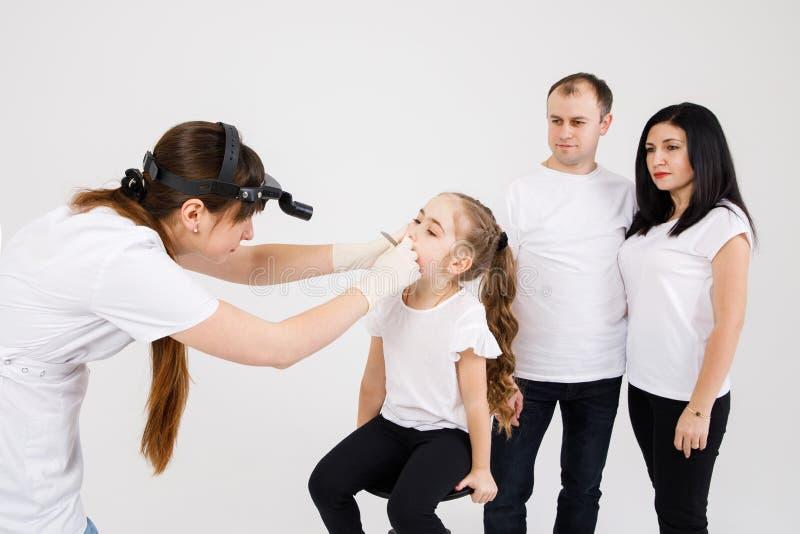 Un doctor de sexo femenino examina la garganta de una muchacha en la cita de un doctor foto de archivo