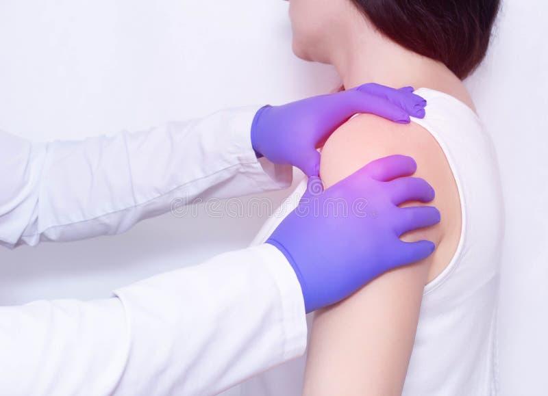 Un doctor examina el hombro dolorido de un paciente con la inflamación y la tiesura en la junta de hombro, polymyalgia, ankylosin imagenes de archivo