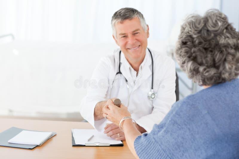 Un doctor mayor con su paciente imagenes de archivo