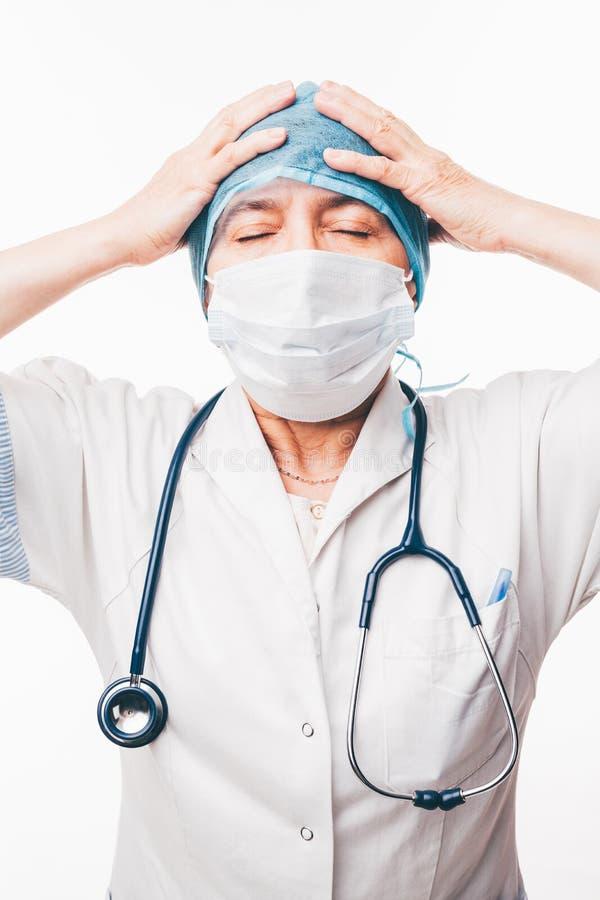 Un doctor muy en cuestión con la máscara y el estetoscopio de la cirugía fotografía de archivo