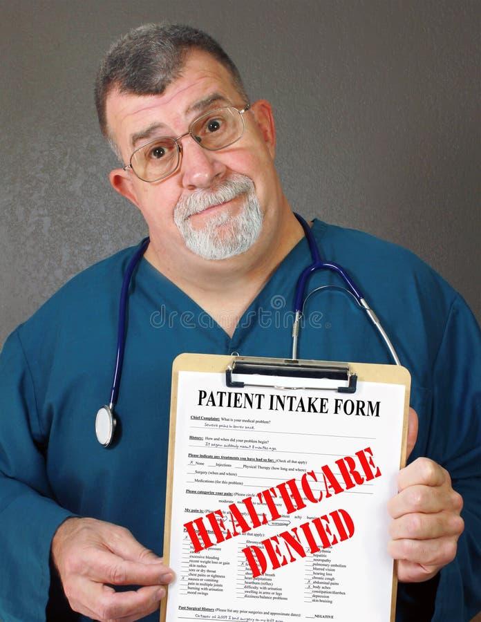 El doctor maduro Displays Healthcare Denied foto de archivo
