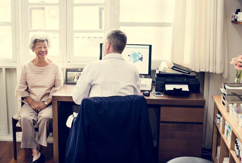 Un doctor paciente mayor de la reunión en el hospital imagen de archivo