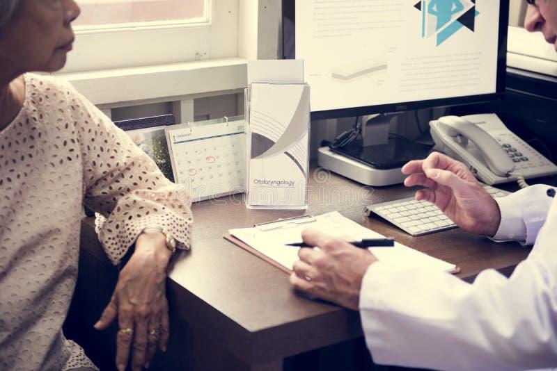 Un doctor paciente mayor de la reunión en el hospital fotos de archivo