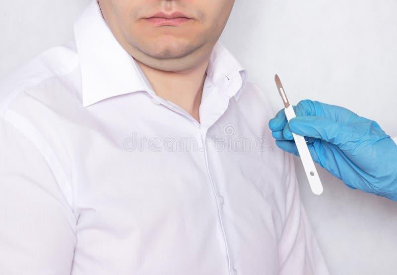 Un doctor sostiene un escalpelo en el fondo de un paciente con una barbilla doble, una cirugía plástica y un plástico foto de archivo libre de regalías
